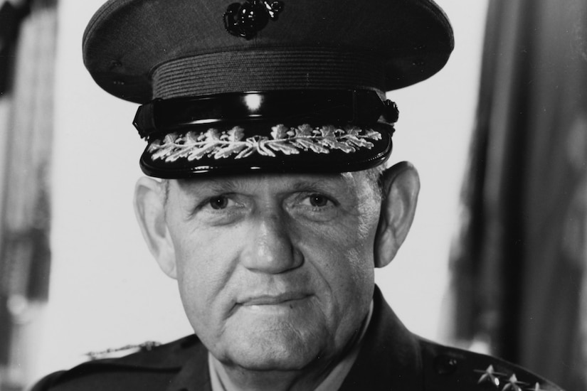 A man in dress uniform and cap poses for a photo.