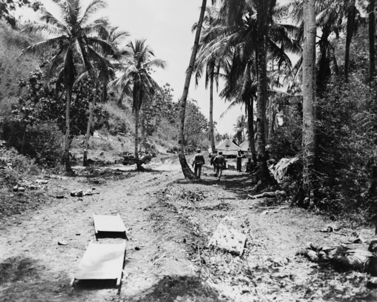 Two stretchers sit in a dirt roadway on a tropical island. A few men can be seen in the background.