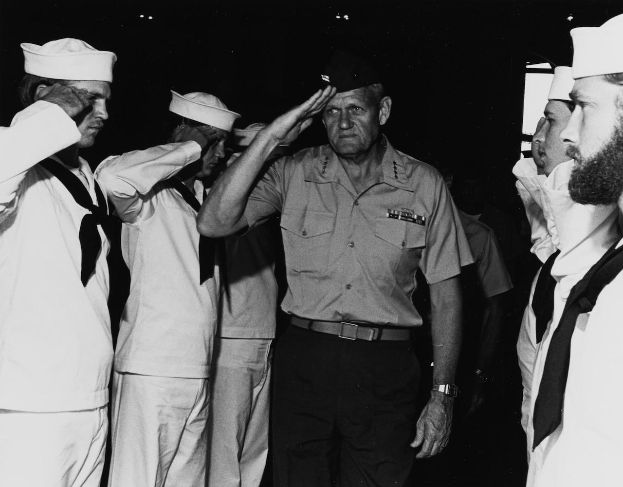 A man in a Marine uniform salutes sailors in dress white uniforms.