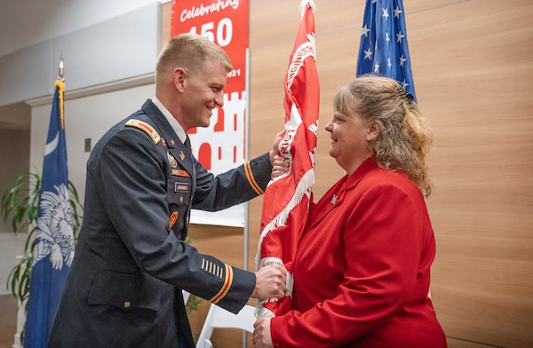 Lt. Col. Andrew Johannes, hands the U.S. Army Corps Of Engineers, Charleston District guidon to Lisa Metheney, Deputy District Engineer for Programs and Project Management, during a change of command ceremony.  Johannes became the district's 89th commander, taking over for outgoing commander Lt. Col. Rachel Honderd.