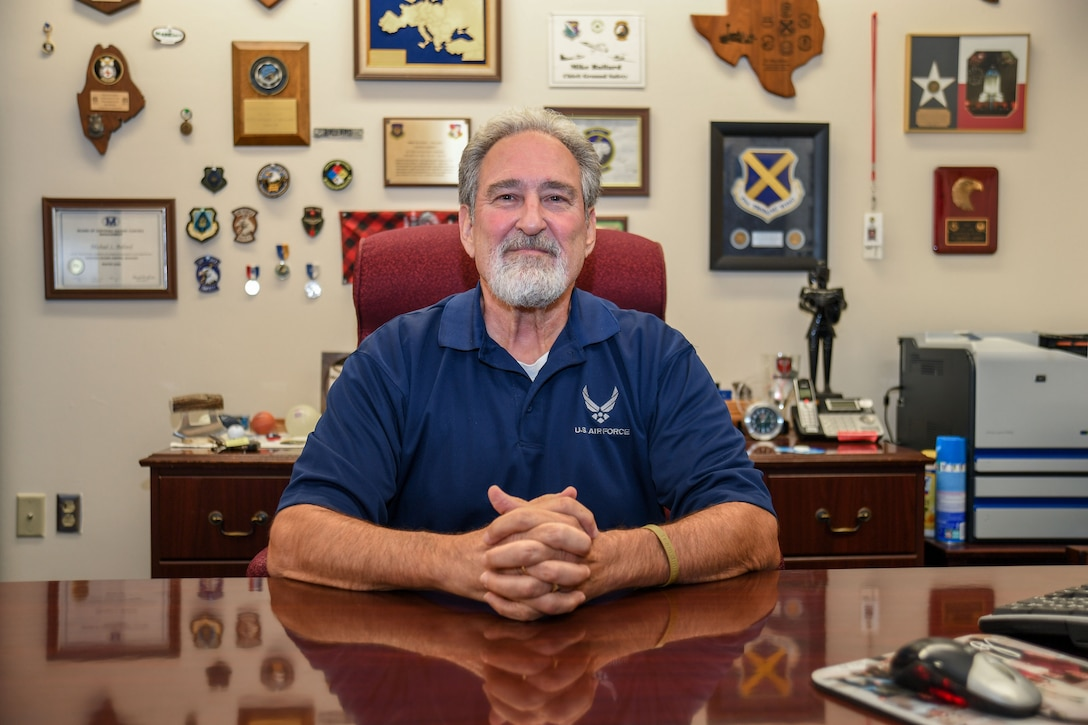 Ballard retires with more than 45 years of service. Photo of Ballard sitting proudly at his desk surrounded by many of his mementos from his years of safeguarding Airmen and Guardians.