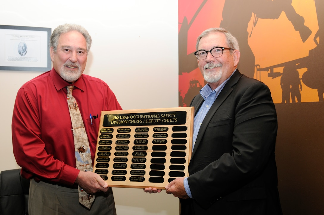 Ballard retires with more than 45 years of service. Photo of Ballard and Parsons holding plaque.