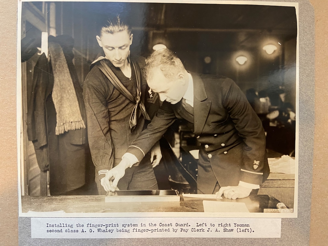 A photo of installing the finger-print system in the Coast Guard.  Left to right Yeoman second class A. G. Whaley being finger-printed by Pay Clerk J. A. Shaw.