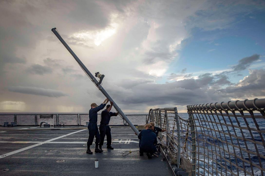 Sailors lift a flag pole on a ship at sea.