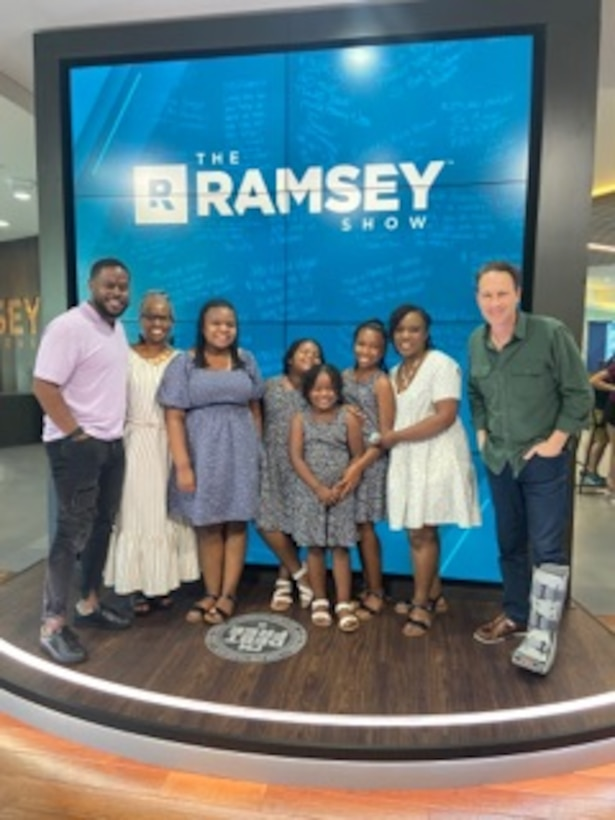 U.S. Air Force Master Sgt. Traci Coston stands next to her family and the hosts of The Ramsey Show on The Ramsey Show set, May 28, 2021. Coston appeared on the show to explain how she paid off $36,000 in student loan and credit card debt in 14 months. She currently serves as the 9th Air Force (Air Forces Central)/Financial Management superintendent and also holds a financial coaching master's certification in personal finance to help others achieve their financial dreams.