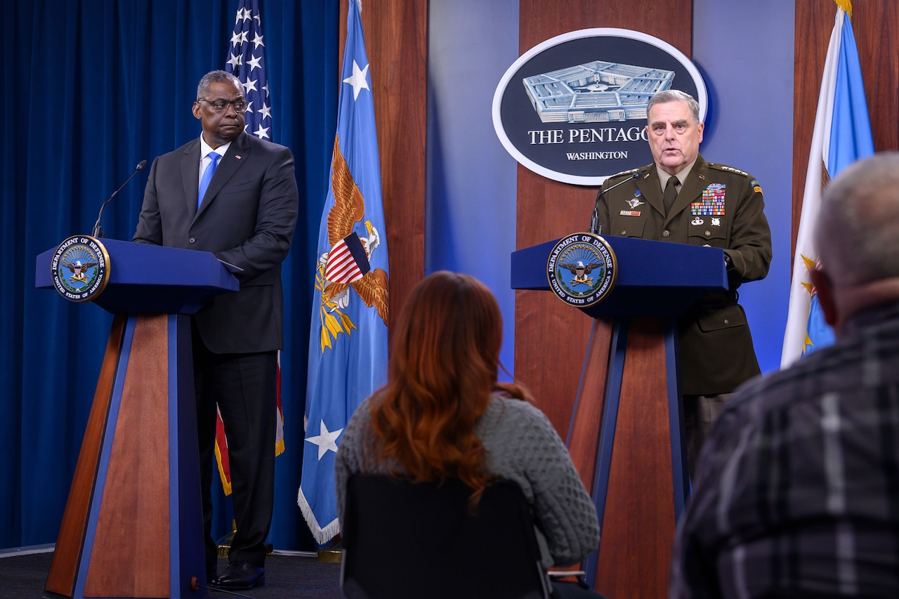 Defense secretary and Joint Chiefs chairman stand at lecterns in front of a seated audience.