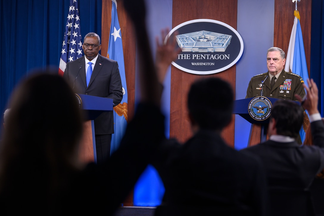 Secretary of Defense and chairman of the Joint Chiefs of Staff stand at lecterns.