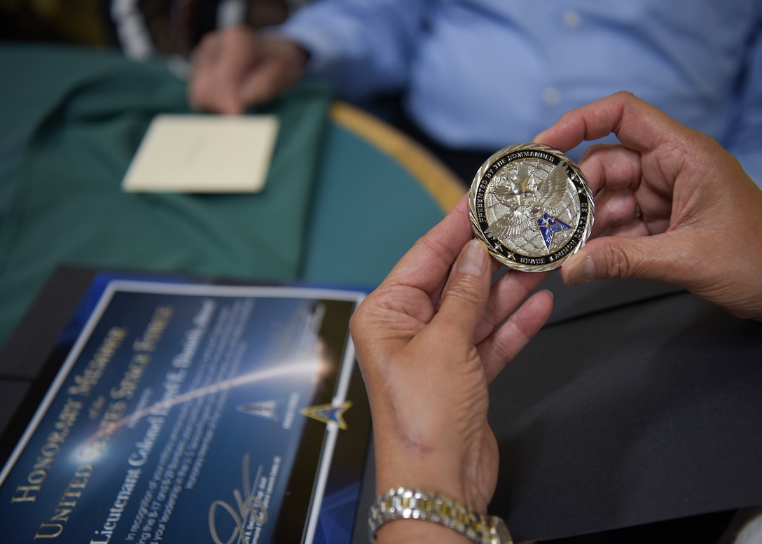 """Family members admire the coin and certificate presented to Lt. Col. Lloyd Daniels, retired Air Force veteran, at his 100th birthday celebration in Orcutt, California, July 16, 2021. Daniels received a coin and an """"Honorary Member of the United States Space Force"""" certificate from Col. Robert Long, Space Launch Delta 30 commander. (U.S. Space Force photo by Airman Kadielle Shaw)"""