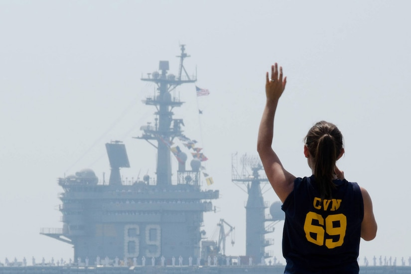 A woman waves as a ship passes in the distance.