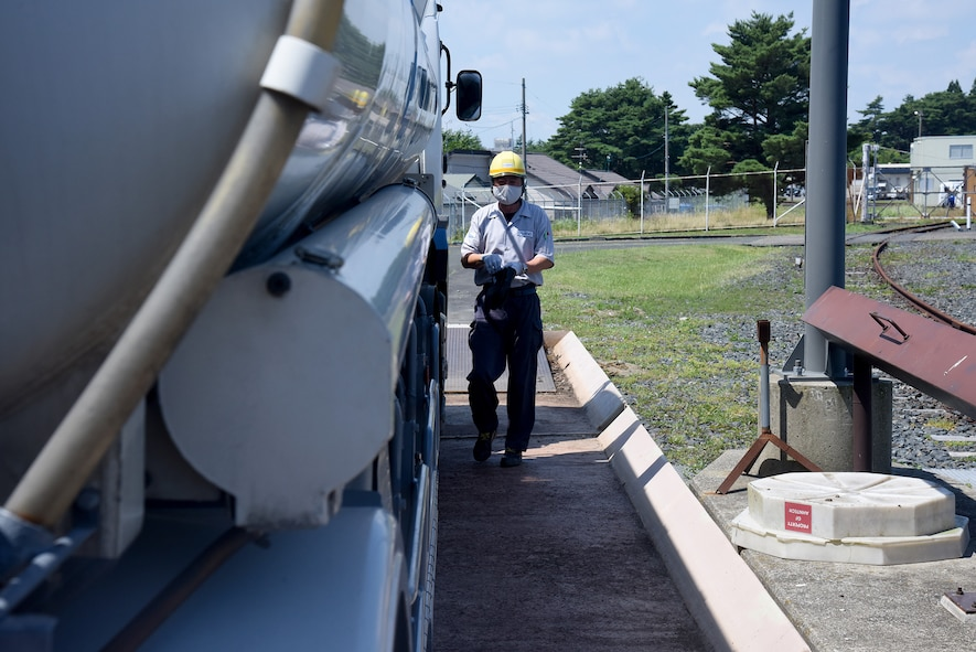 A man walks beside a fuel truck and prepares to unload fuel.