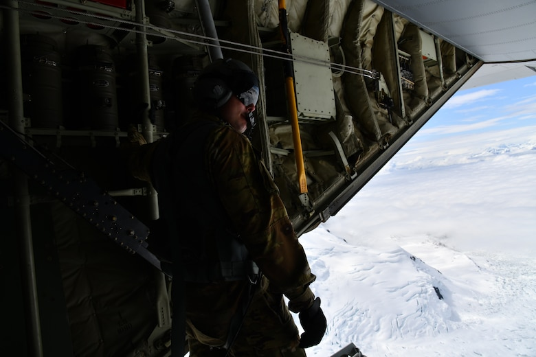 Tech. Sgt. Jacob Fountain, 815th Airlift Squadron loadmaster, holds on after opening the cargo door ramp while the pilots conduct low-level tactical flight training patterns during a training exercise at Joint Base Elmendorf-Richardson, Alaska, July 13-16, 2021. The terrain of the mountain, valleys and along with the colder temperatures provided a different challenge for the low-level flights, which were an effective tactic in training for hostile environments.  (U.S. Air Force photo by Master Sgt. Jessica Kendziorek)
