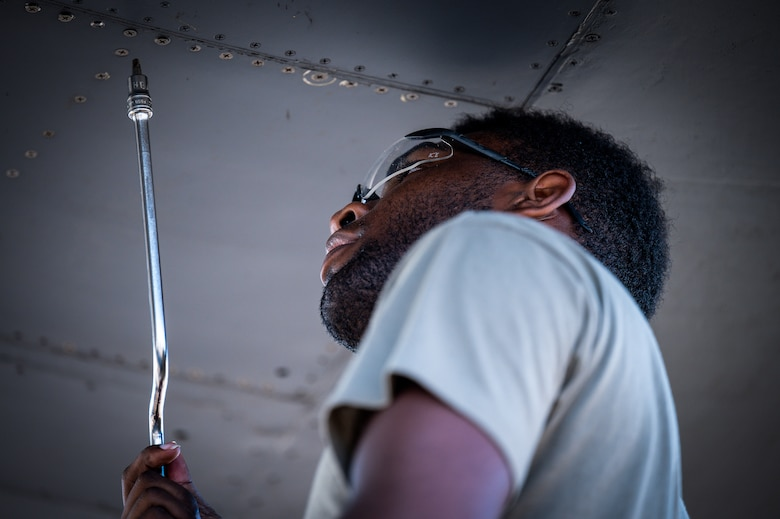 An Airman from Dyess Air Force Base, Texas, removes a panel from a B-1B Lancer's wing at Barksdale Air Force Base, Louisiana, July 7, 2021.