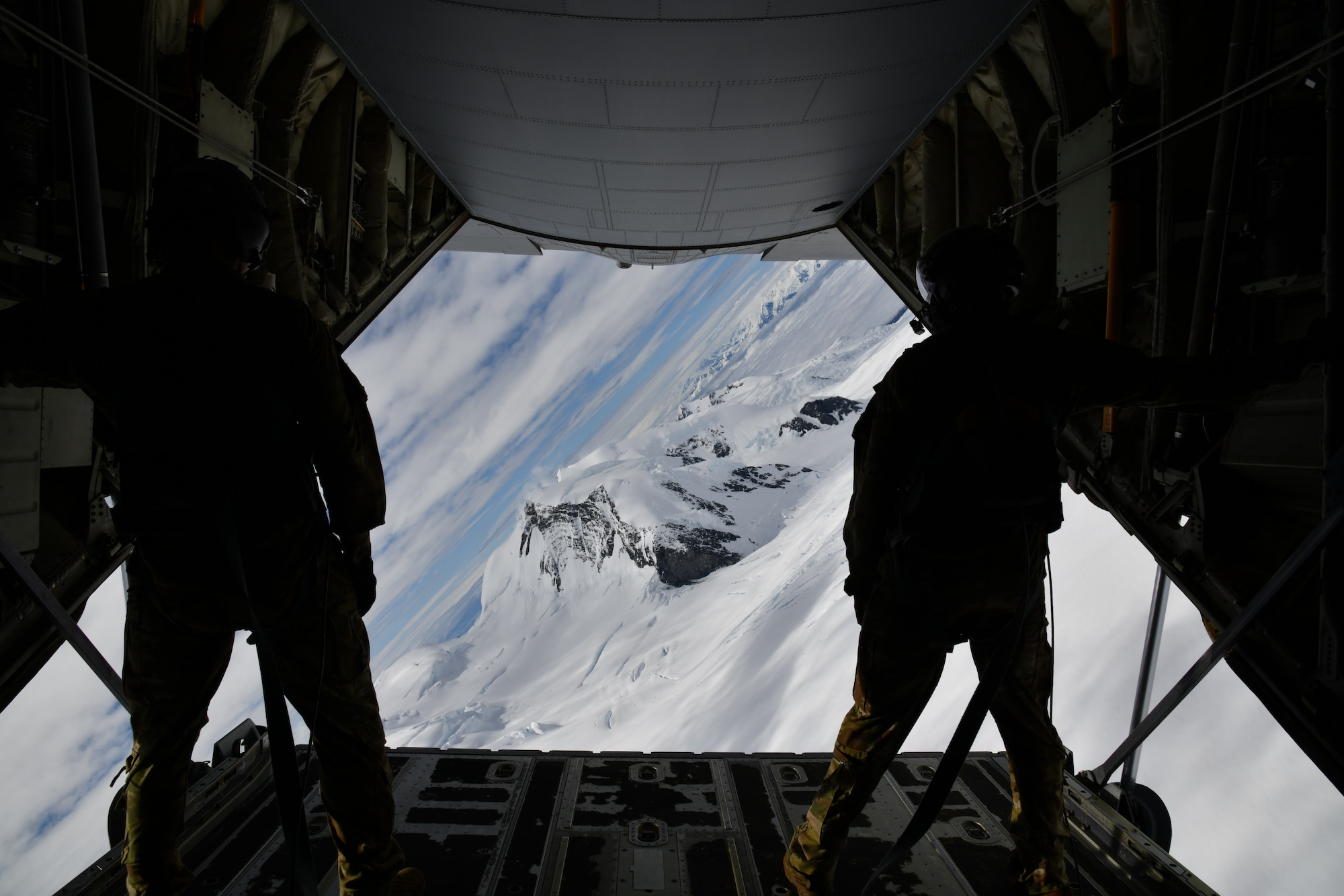 Tech. Sgt. Jacob Fountain (left) and Master Sgt. Gary Bryant (right), 815th Airlift Squadron loadmasters, hold on after opening the cargo door ramp while the pilots conduct low-level tactical flight training patterns during a training exercise at Joint Base Elmendorf-Richardson, Alaska, July 13-16, 2021. The terrain of the mountain, valleys and along with the colder temperatures provided a different challenge for the low-level flights, which were an effective tactic in training for hostile environments. (U.S. Air Force photo by Master Sgt. Jessica Kendziorek)