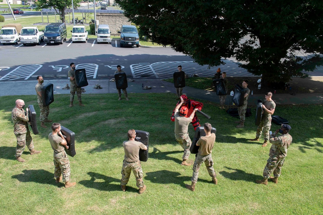 Airmen from the 374th Mission Support Group take turns fighting Senior Airman Tyler Gutierrez, 374th Security Forces Squadron training instructor, during a 374th MSG training day at Yokota Air Base, Japan, July 21, 2021.