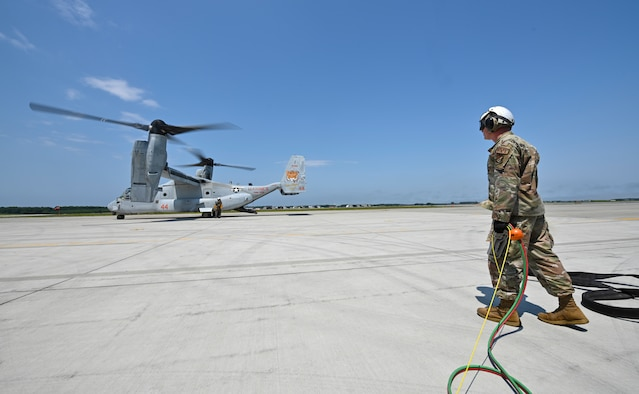 An Airman stands with cables in his hand looking at a tiltrotor aircraft.