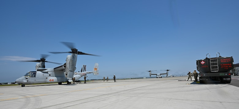 Service members stand next to a fuel truck separated from two tiltrotor aircraft.
