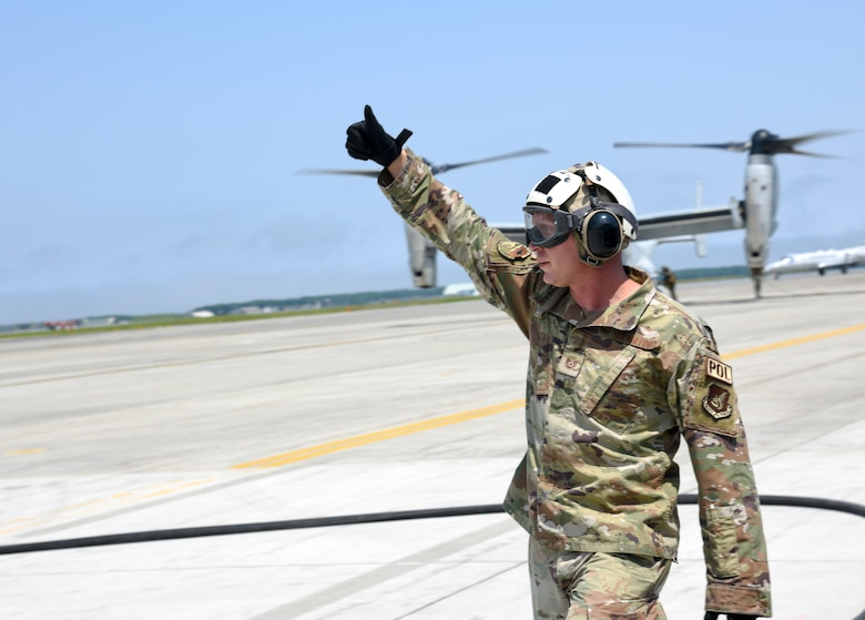 An Airman raises his arm above his head as he gives a thumbs up.
