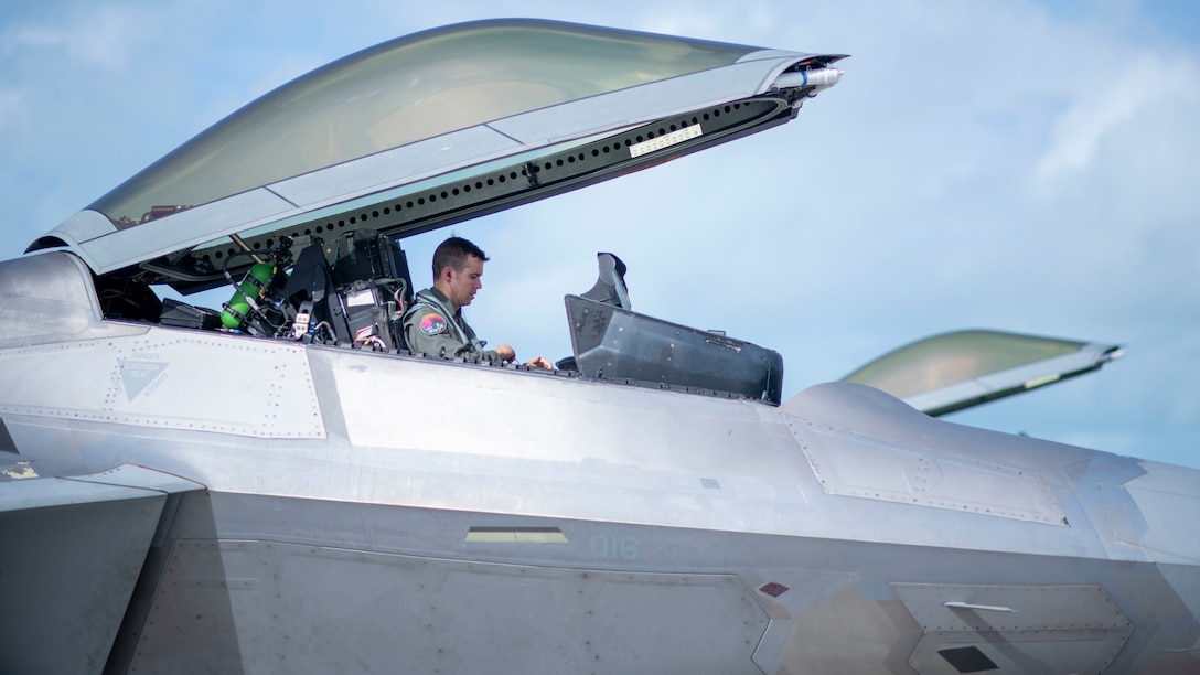 A pilot sits in an F-22 Raptor with the canopy open