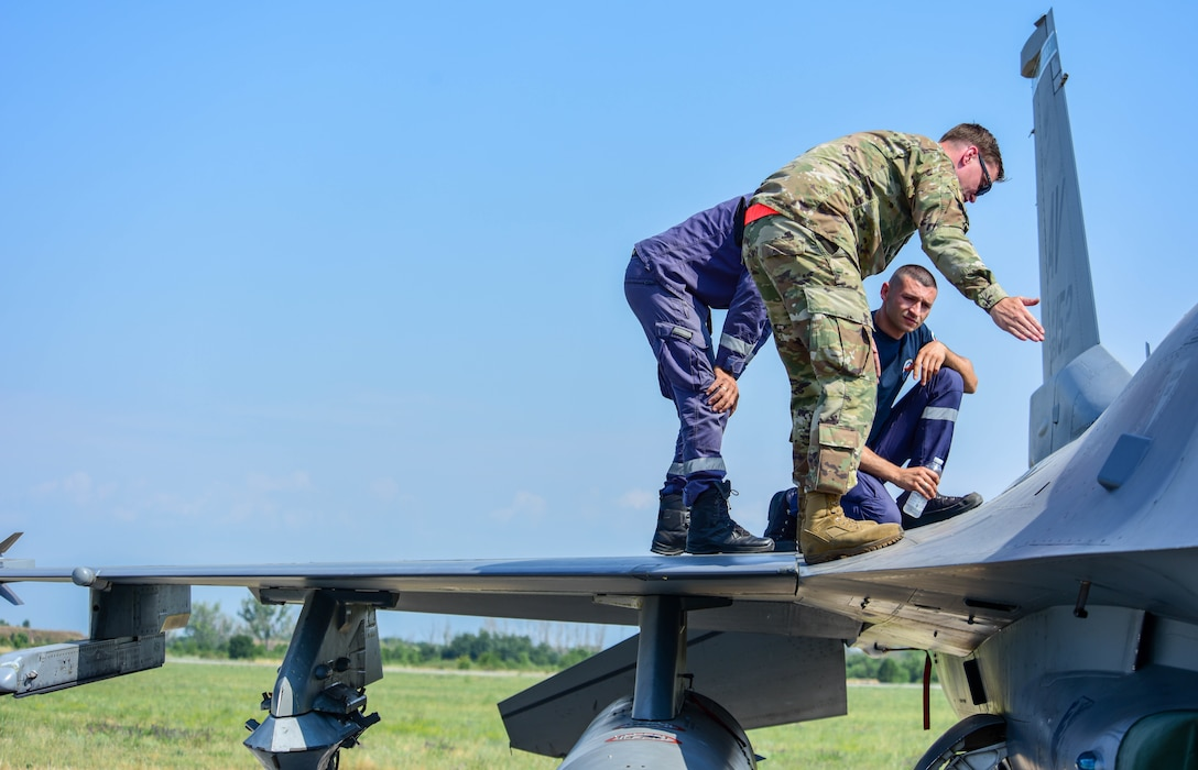 U.S. Air Force Staff Sgt. Jason Anders, 31st Maintenance Squadron aircraft fuels system craftsman, teaches Bulgarian air force members hydrazine emergency response procedures on a U.S. Air Force F-16 Fighting Falcon assigned to the 555th Fighter Squadron during exercise Thracian Star 21 at Graf Ignatievo Air Base, Bulgaria, July 20, 2021. This exercise required all levels of a squadron to deploy small teams of Airmen and aircraft for a short amount of time to hone their skills. Thracian Star 21 also enhanced their ability to rapidly deploy to a remote location, establish command and control and deliver lethal airpower more effectively and efficiently anywhere in the world. (U.S. Air Force photo by Airman 1st Class Brooke Moeder)