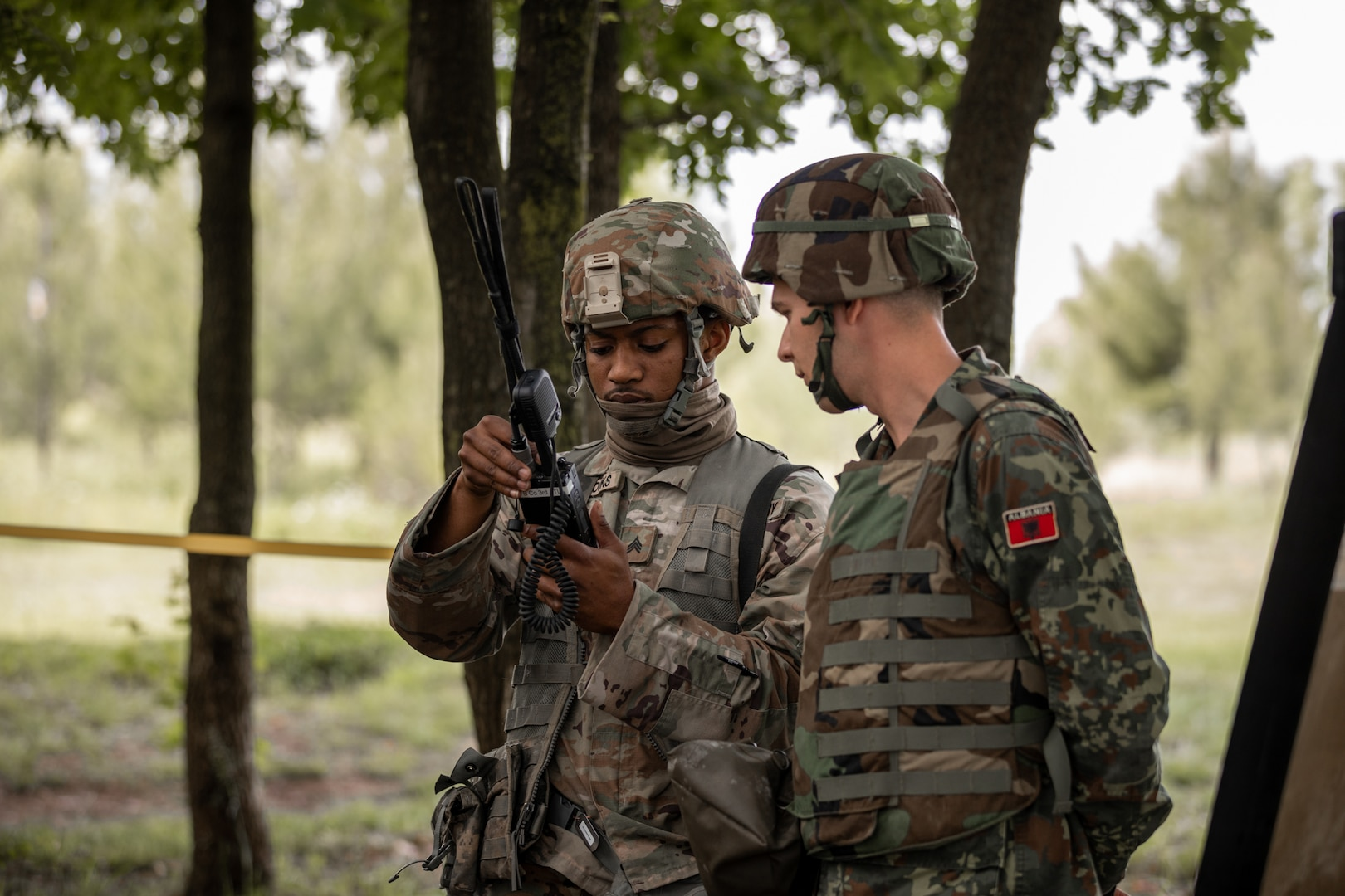 A Florida Army National Guard Soldier shows an Albanian cadet how to program a radio during DEFENDER-Europe 21-linked exercise Immediate Response May 18, 2021.