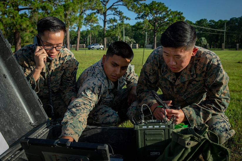 Three Marines kneel on the ground and work with a radio system.