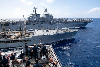 Officers aboard the Whidbey Island-class dock landing ship USS Germantown (LSD 42) station alongside the Henry J. Kaiser-class underway replenishment oiler USNS Rappahannock  (T-AO 204) to receive fuel during a replenishment at sea.