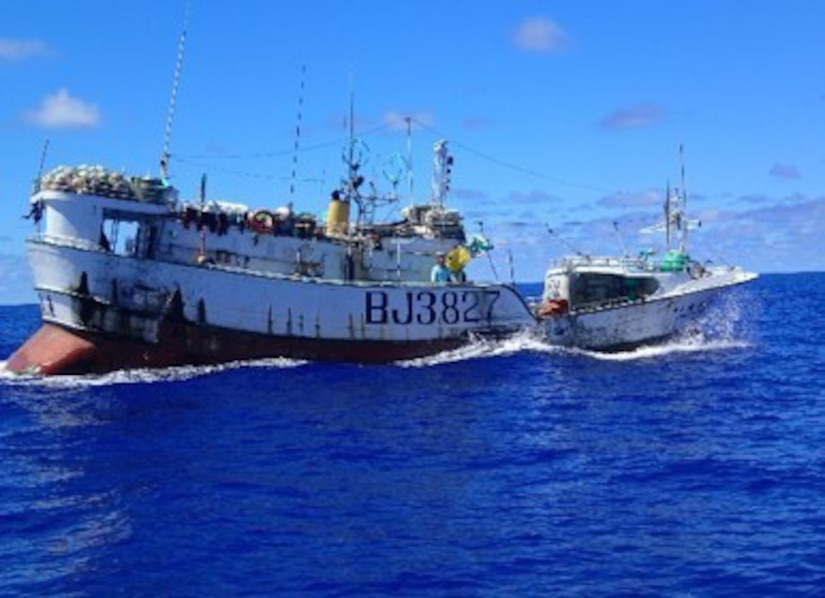 A fishing vessel bobs in the sea.