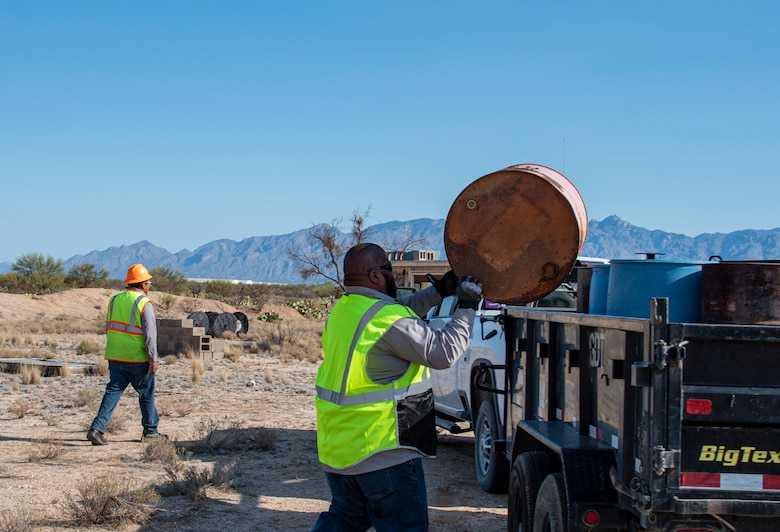 People loading drums into truck.