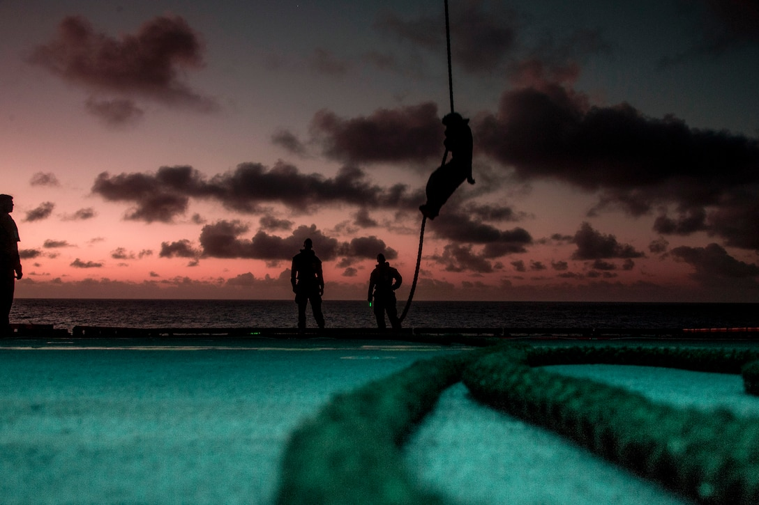 A Marine, shown in silhouette, maneuvers on a rope above a ship's deck as other Marines watch.