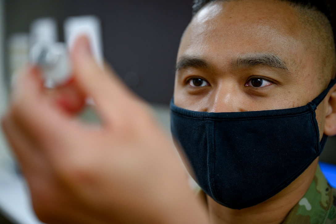 An airman wearing a facemask looks at a vial he's holding.