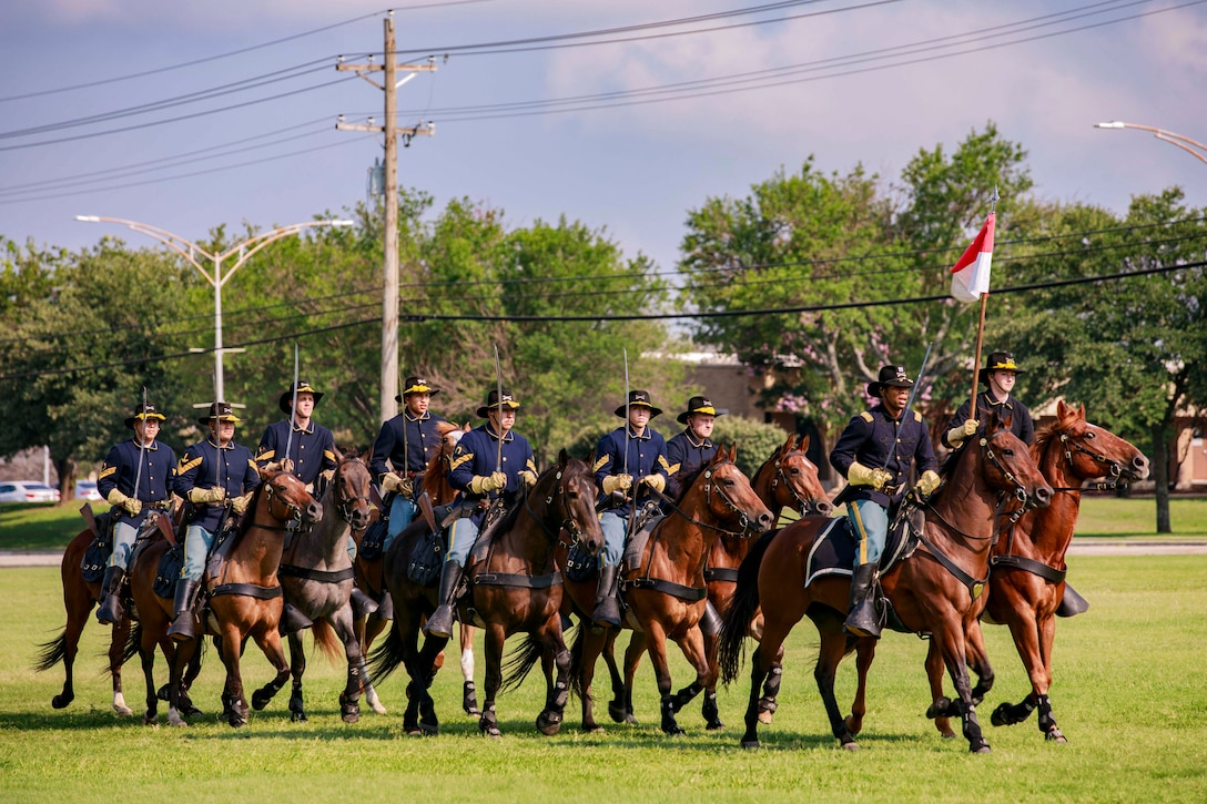 Soldiers ride horses with flags and swords in a field with trees in the background.