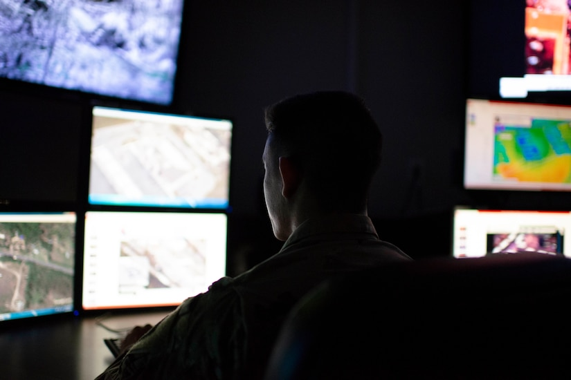 Individuals sit in a darkened room lit only by computer screens.