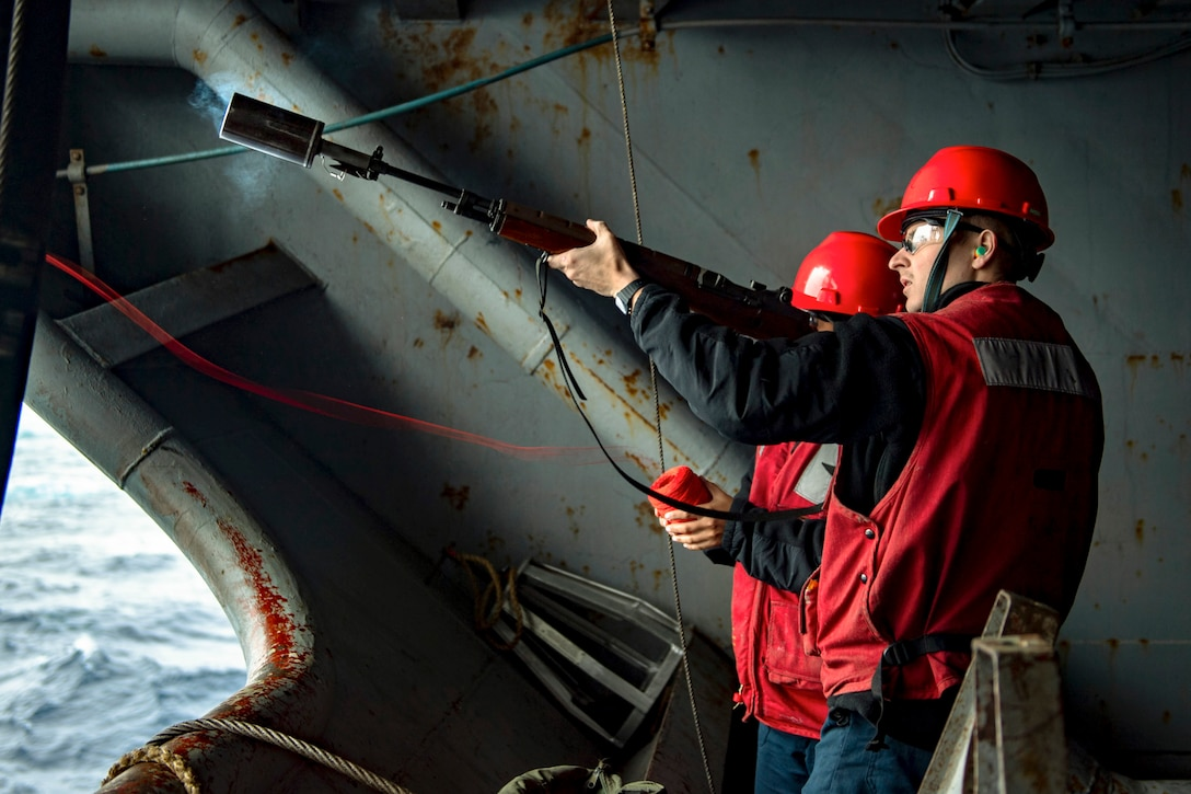 A sailor fires a line from the end of a weapon from inside a ship.