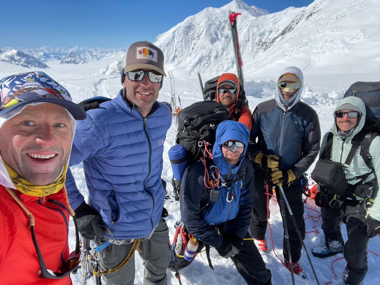 Six men clad in heavy winter gear pose for a photo on a snowy mountainside.