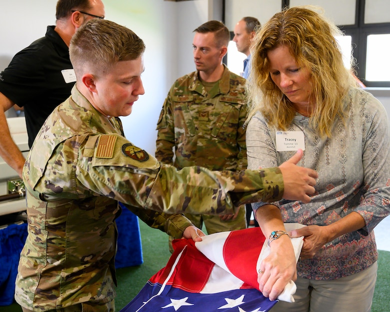 Airman 1st Class Blake Cassick of Wright-Patterson Air Force Base's Honor Guard shows Tracey Tomme how to ceremoniously fold the flag July 14. A Leadership Dayton program member, Tomme was part of the group tour allowing participants to learn about the base's capabilities and its community contributions. (U.S. Air Force photo by R.J. Oriez)