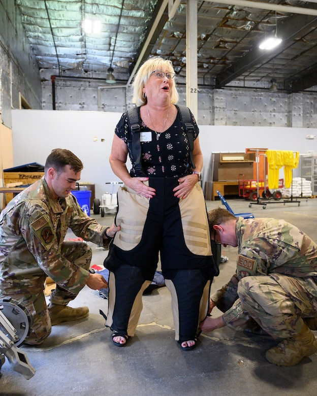 Senior Airman Johnathon Jones (left) and Airman 1st Class Christian Davis, of the 788th Civil Engineer Squadron's Explosive Ordnance Disposal Flight, help Beth Duncan into a bomb suit July 14 at Wright-Patterson Air Force Base. A Leadership Dayton program member, Duncan was part of the group tour allowing participants to learn about the base's capabilities and its community contributions. (U.S. Air Force photo by R.J. Oriez)