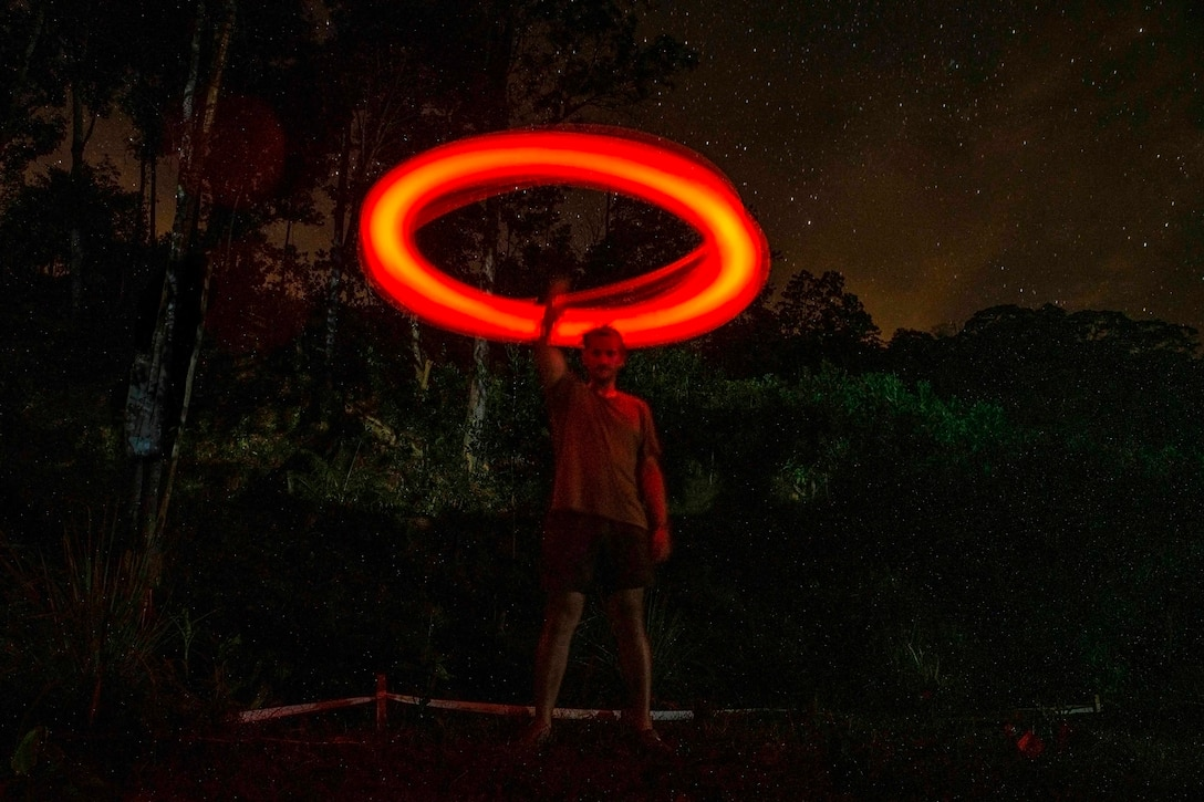 An airman swings a red light stick in a circle over his head at night.