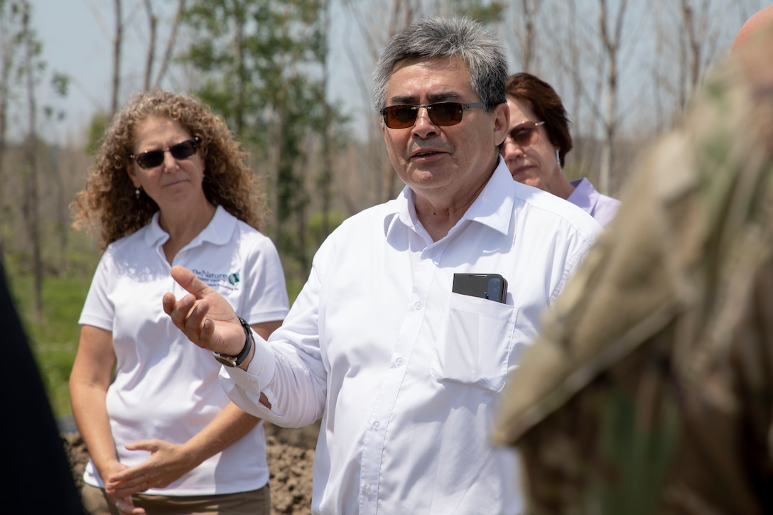 A man in a white shirt talks to a group of people.