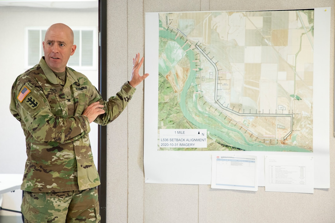 A man in an Army uniform pointing at a map of the L536 levee.