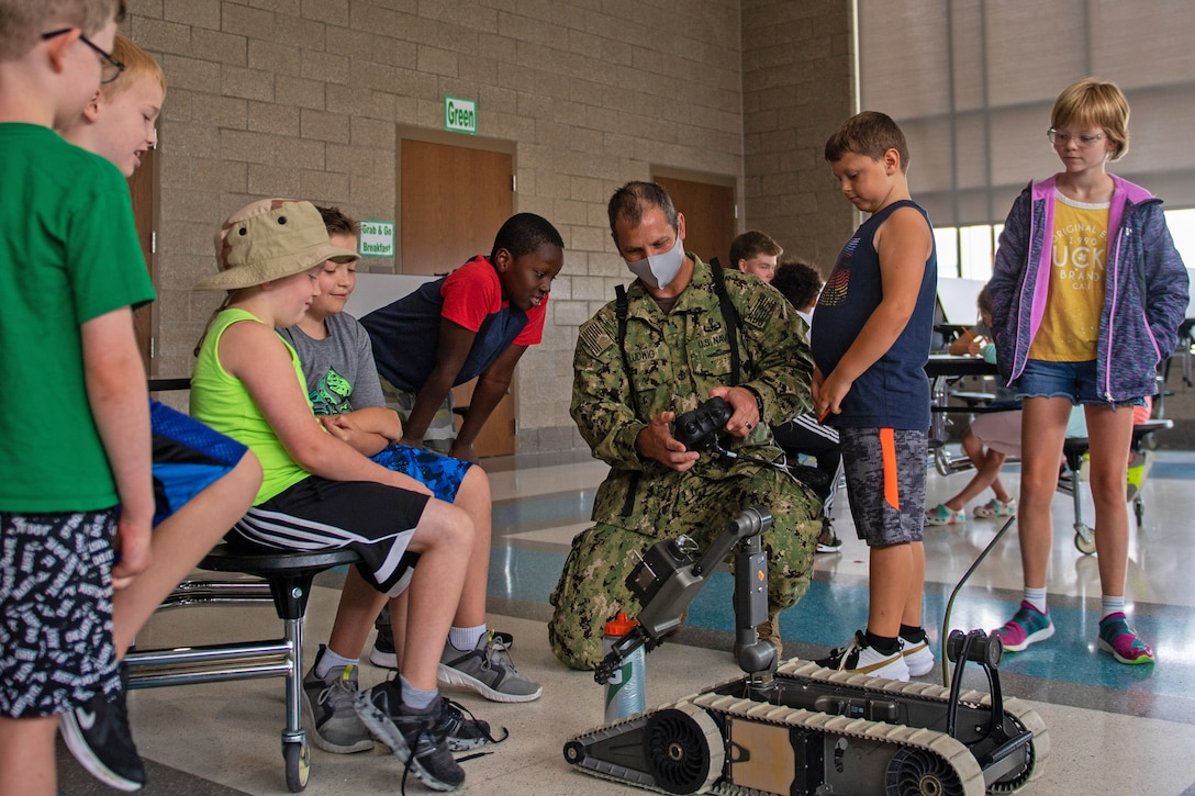 Children stand around a sailor kneeling to demonstrate a robot and remote.