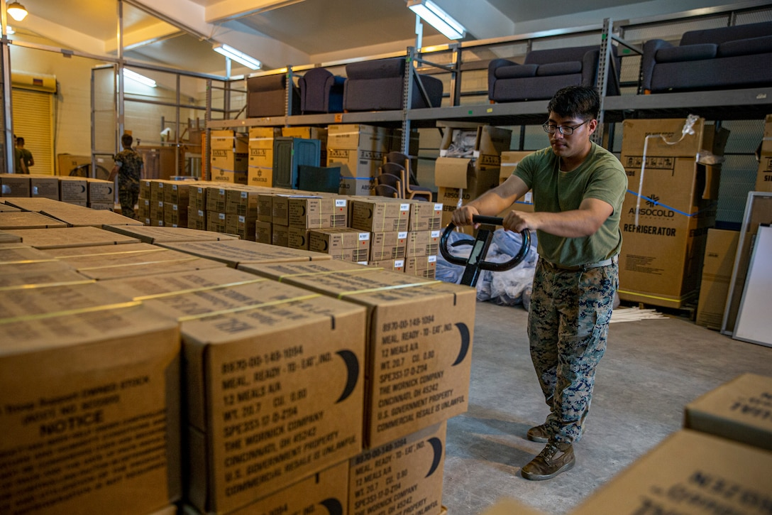 U.S. Marine Corps Lance Cpl. Edwin Carino, a distribution management specialist with Headquarters and Support Battalion, Marine Corps Installations Pacific, transports meals, ready to eat (MRE's) on Camp Lester, Okinawa, Japan, July 19, 2021. In preparation for Typhoon In-Fa, Camp Foster Camp Services provide units with MRE's, base preparation services, sandbags, and bulk trash storage to keep service members safe and prepared during typhoon season in Okinawa. Carino is a native of Rariden, New Jersey. (U.S. Marine Corps photo by Lance Cpl. Alex Fairchild)