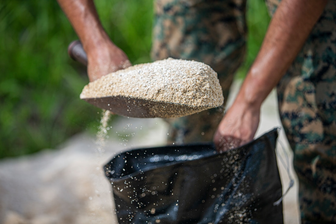 U.S. Marine Corps Pfc. Victor Magana, a motor transportation technician with 3d Transportation Battalion, 3d Marine Logistics Group, fills a sandbag on Camp Foster, Okinawa, Japan, July 19, 2021. In preparation for Typhoon In-Fa, Camp Foster Camp Services provide units with MRE's, base preparation services, sandbags, and bulk trash storage to keep service members safe and prepared during typhoon season in Okinawa. Magana is a native of Santa Paula, California. (U.S. Marine Corps photo by Lance Cpl. Alex Fairchild)