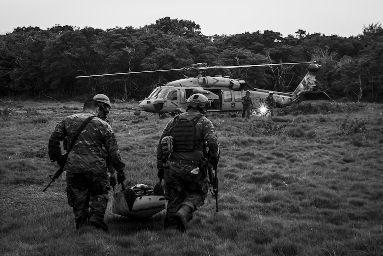 """U.S. Air Force Airmen assigned to the 154th Fighter Wing, Hawaii Air National Guard carry a """"fallen comrade"""" in a litter to a U.S. Navy Helicopter Sea Combat Squadron 25 helicopter as part of combat readiness training course during Operation Pacific Iron 2021, July 20, 2021, at Andersen Air Force Base, Guam."""