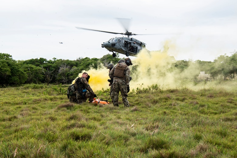 """U.S. Air Force Airmen assigned to the 154th Fighter Wing, Hawaii Air National Guard wait with a """"fallen comrade"""" in a litter to practice medical evacuation with U.S. Navy Helicopter Sea Combat Squadron 25 as part of a combat readiness training course during Operation Pacific Iron 2021, July 20, 2021, at Andersen Air Force Base, Guam."""