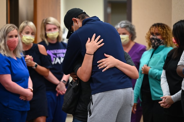 Senior Airman Eleazar Hernandez, 2nd Maintenance Squadron aerospace ground equipment journeyman, hugs his spouse after his final chemotherapy treatment at the CHRISTUS Health Shreveport-Bossier medical center, Louisiana, July 2, 2021. Hernandez fought cancer for 6 months before entering remission. (U.S. Air Force photo by Airman 1st Class Jonathan E. Ramos)