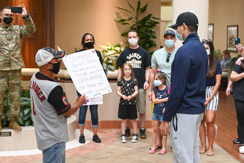 Senior Airman Eleazar Hernandez, 2nd Maintenance Squadron aerospace ground equipment journeyman, receives a morale gift after his final chemotherapy treatment at the CHRISTUS Health Shreveport-Bossier medical center, Louisiana, July 2, 2021. Hernandez fought cancer for 6 months before entering remission. (U.S. Air Force photo by Airman 1st Class Jonathan E. Ramos)