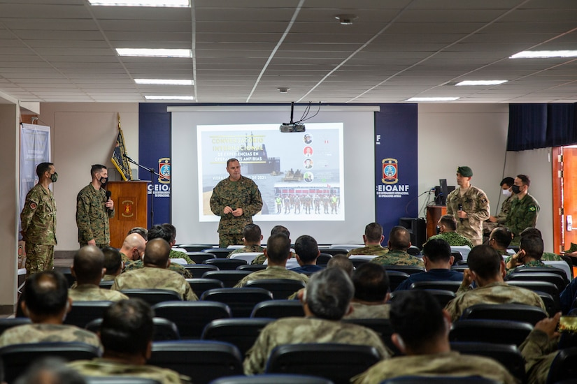 Marines talk in front of an audience.