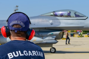 A Bulgarian air force member looks at a U.S. Air Force F-16 Fighting Falcon assigned to the 555th Fighter Squadron during exercise Thracian Star 21 at Graf Ignatievo Air Base, Bulgaria, July 16, 2021. Thracian Star 21 is a Bulgarian air force-led exercise aiming to enhance interoperability and the ability to rapidly deploy to remote locations. (U.S. Air Force photo by Airman 1st Class Brooke Moeder)