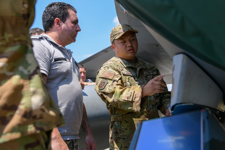 Senior Airman James Xiong, 31st Civil Engineer Squadron fire department driver operator, right, teaches Bulgarian air force members F-16 Fighting Falcon emergency response procedures during exercise Thracian Star 21 at Graf Ingatievo Air Base, Bulgaria, July 20, 2021. Participation in Thracian Star 21 offers an opportunity for Airmen to train and hone in on operational and tactical skills. (U.S. Air Force photo by Airman 1st Class Brooke Moeder)