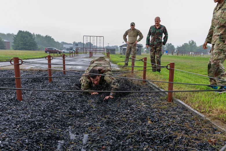 Senior Airman Trevor Thompson, a reservist in the 67th Aerial Port Squadron, navigates under an obstacle on the land obstacle course at Camp Johnson, Vermont as part of the team selection and training event